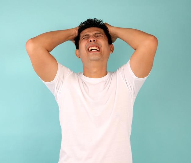 Retrato de um jovem asiático decepcionado, concentrando-se em homens de camiseta branca e azul.