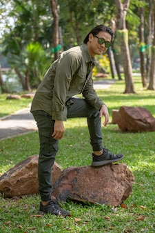 Retrato de um jovem asiático feliz com camisa de manga comprida e calça verde em pé no parque