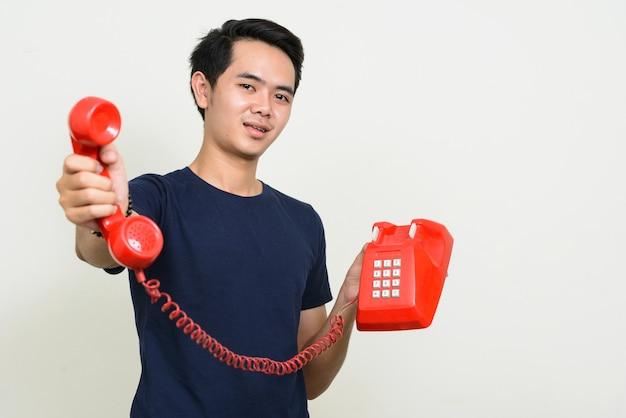 Retrato de um jovem asiático feliz dando um telefone antigo