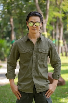 Retrato de um jovem asiático feliz em uma camisa de manga comprida e calça verde em pé no parque