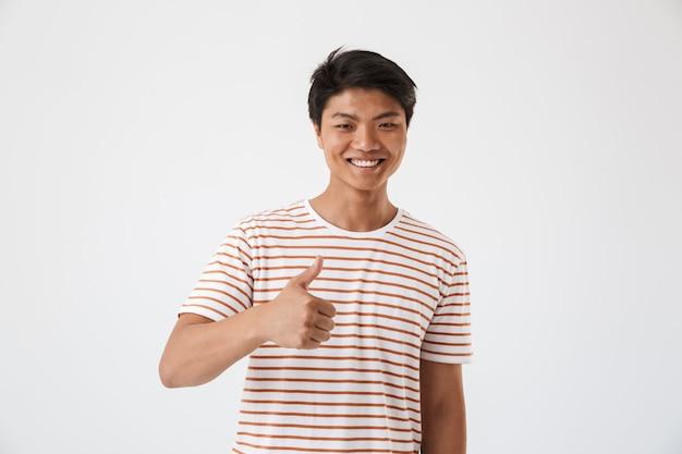 Retrato de um jovem asiático feliz mostrando os polegares para cima
