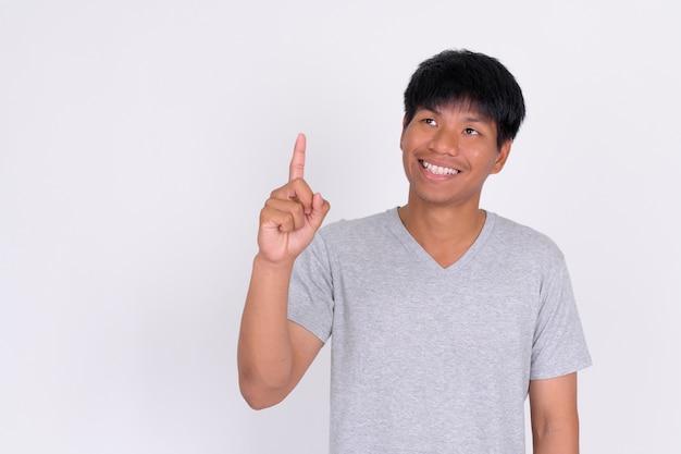 Retrato de um jovem asiático feliz pensando e apontando para cima