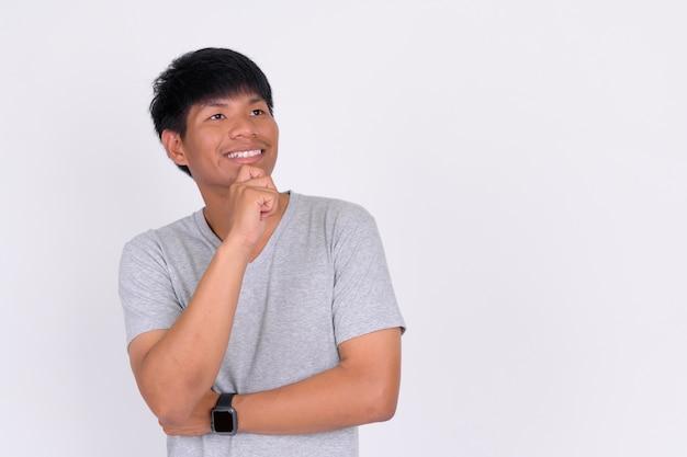 Retrato de um jovem asiático feliz pensando e olhando para cima