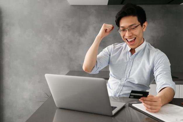 Retrato de um jovem asiático feliz segurando o cartão de crédito