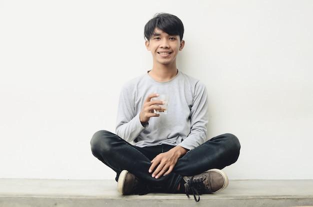 Retrato de um jovem asiático feliz tomando café