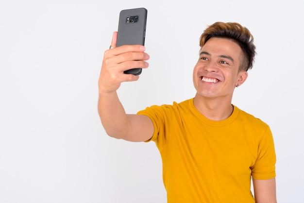 Retrato de um jovem asiático feliz tomando selfie no telefone contra uma parede branca