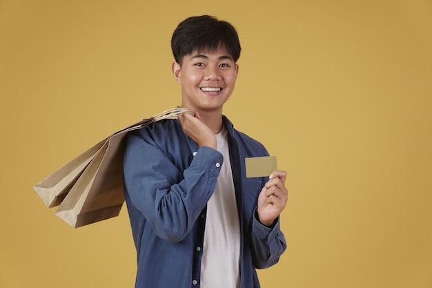 Retrato de um jovem asiático feliz vestido casualmente, segurando sacolas de compras e cartão de crédito isolado
