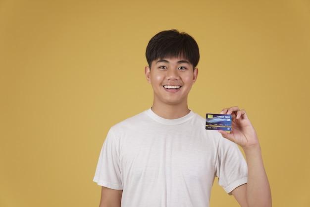 Retrato de um jovem asiático feliz vestido casualmente, segurando um cartão de crédito isolado para fazer compras.