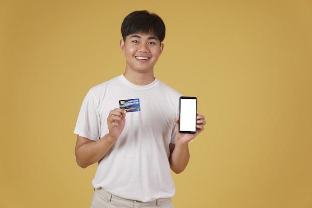 Retrato de um jovem asiático feliz vestido casualmente, segurando um smartphone e um cartão de crédito isolado para fazer compras online