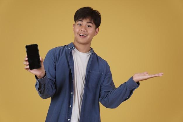 Retrato de um jovem asiático feliz vestido de forma casual e sorrindo mostrando a tela do smartphone em branco