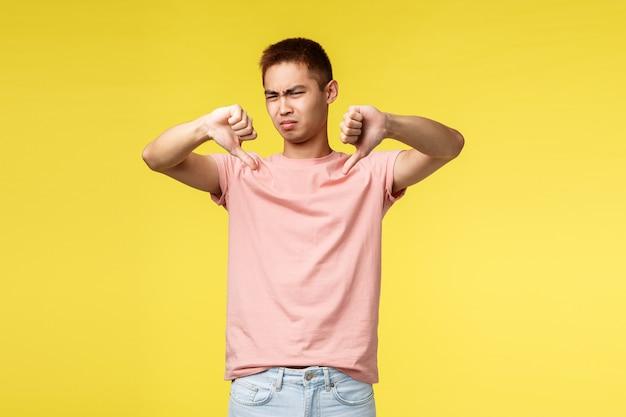 Retrato de um jovem asiático, mostrando o gesto sobre parede amarela