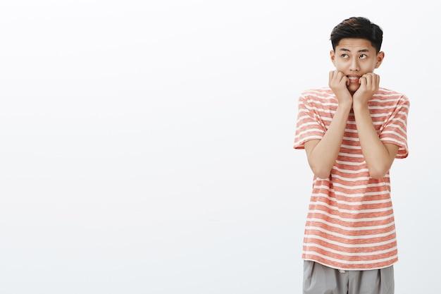 Retrato de um jovem asiático nervoso e assustado em uma camiseta listrada, mordendo os dedos, olhando para o canto superior esquerdo, inseguro e preocupado