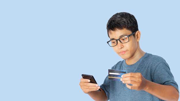 Retrato de um jovem asiático, usando um smartphone com cartão de crédito.