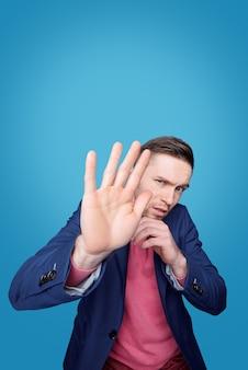 Retrato de um jovem assustado franzindo a testa e escondendo o rosto atrás da mão