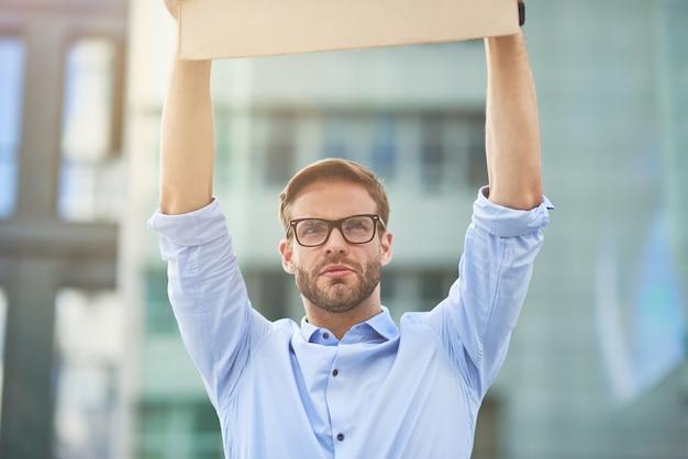 Retrato de um jovem ativista do sexo masculino, caucasiano, vestindo camisa azul e óculos vazios