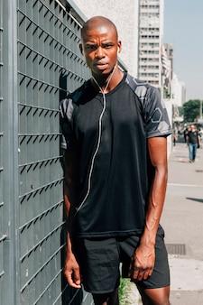 Retrato, de, um, jovem, atleta masculino, inclinar-se, portão, com, fones ouvido, em, seu, orelhas