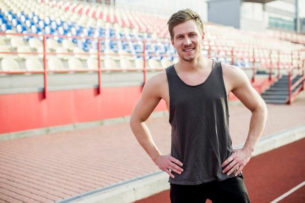 Retrato de um jovem atleta masculino sorridente no estádio