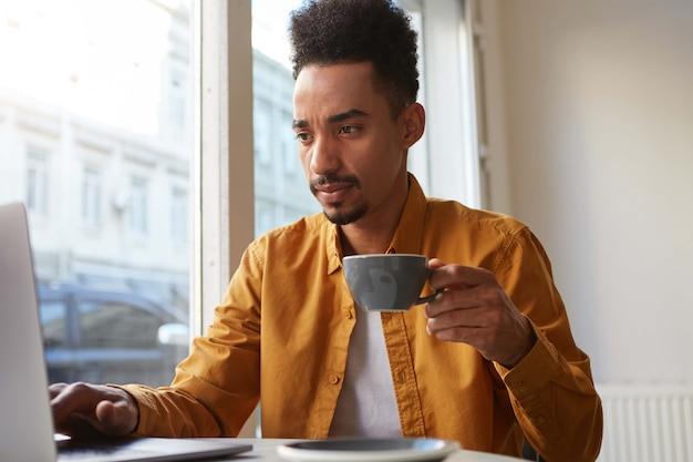 Retrato de um jovem atraente afro-americano, trabalha em um laptop em um café, bebe café e olha pensativamente para o monitor, concentra-se em seu trabalho.
