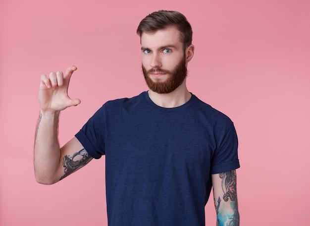 Retrato de um jovem atraente de barba vermelha, vestindo uma camiseta azul, carrancudo e olhando para a câmera, mostra aos dedos algo pequeno isolado sobre um fundo rosa.