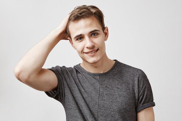 Retrato de um jovem atraente em uma camisa cinza, tocando seu cabelo.