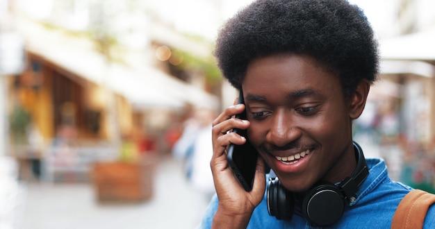 Retrato de um jovem atraente falando com o smartphone ao ar livre enquanto usa o telefone celular.