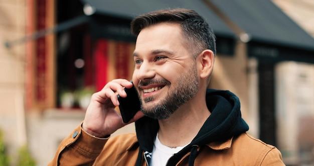 Retrato de um jovem atraente falando smartphone ao ar livre, lindo cara caucasiano, usando ...