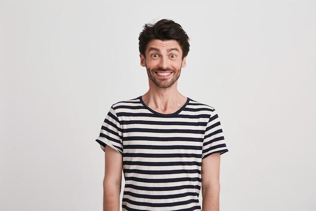 Retrato de um jovem atraente feliz com cerdas usando uma camiseta listrada se sentindo animado e sorrindo, isolado no branco