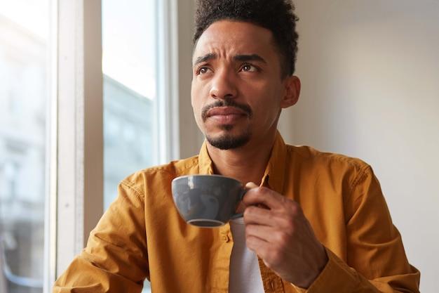 Retrato de um jovem atraente garoto afro-americano que pensa, bebe café aromático de uma xícara cinza, tentando se lembrar de algo e olha para cima pensativamente.