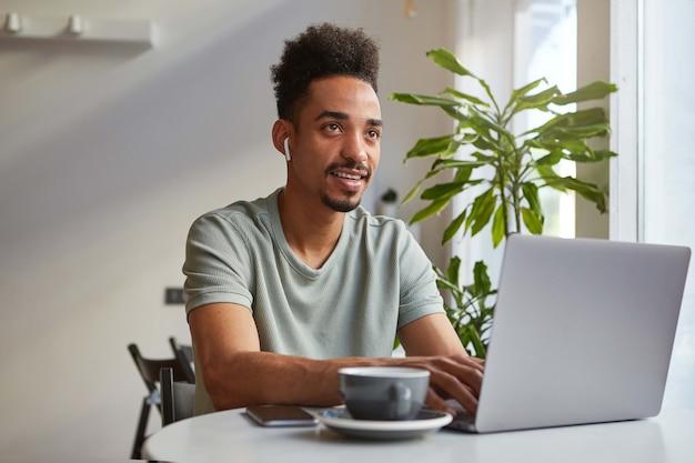 Retrato de um jovem atraente garoto afro-americano que pensa, senta-se à mesa em um café e trabalha em um laptop