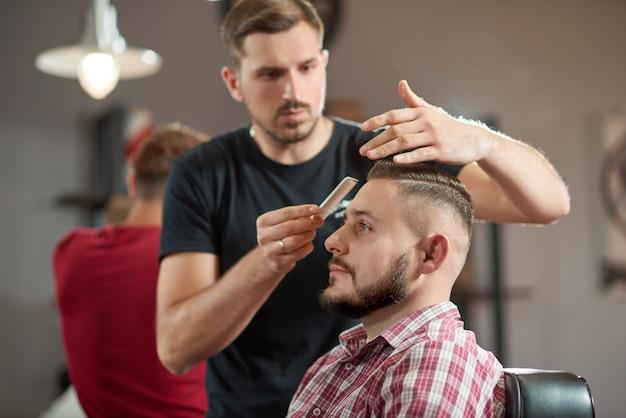 Retrato de um jovem barbeiro estilizando o cabelo de seu cliente barbudo.
