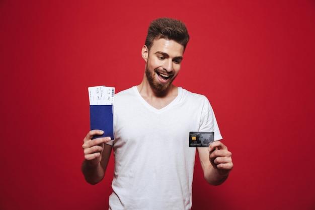 Retrato de um jovem barbudo alegre segurando um passaporte