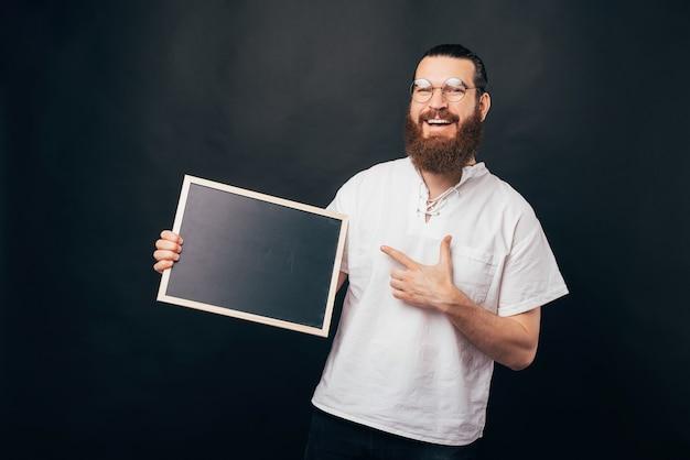 Retrato de um jovem barbudo alegre usando óculos redondos e apontando para o quadro negro vazio