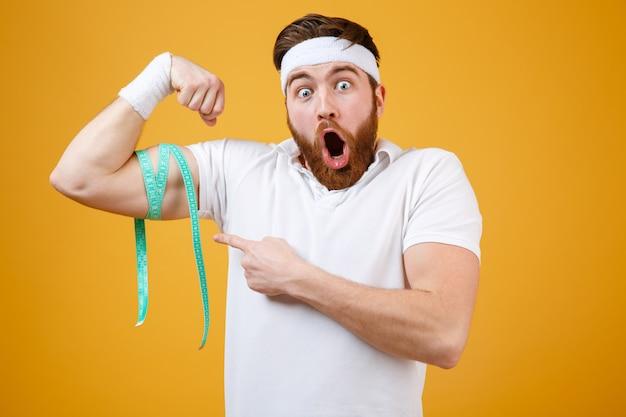 Retrato de um jovem barbudo animado fitness homem medindo bíceps