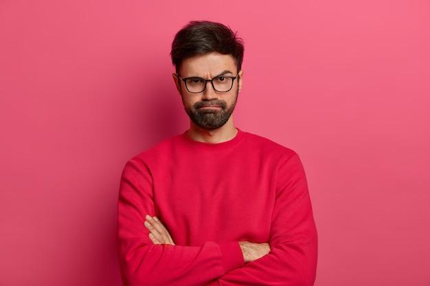 Retrato de um jovem barbudo atraente mantém as mãos cruzadas, faz opinião negativa sobre algo, sorri de insatisfação, alguém irritado conta mentiras, usa óculos escuros e suéter vermelho.