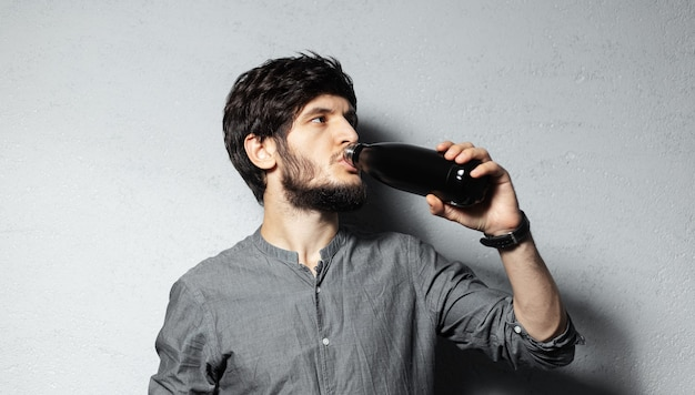 Retrato de um jovem barbudo bebendo água de uma garrafa preta de aço inoxidável