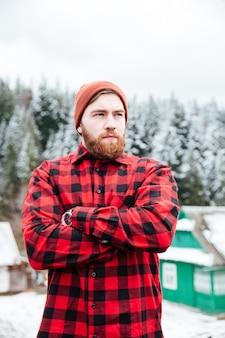 Retrato de um jovem barbudo bonito com chapéu vermelho e camisa quadriculada em pé com os braços cruzados