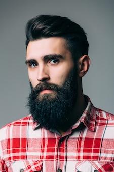 Retrato de um jovem barbudo bonito isolado na parede cinza