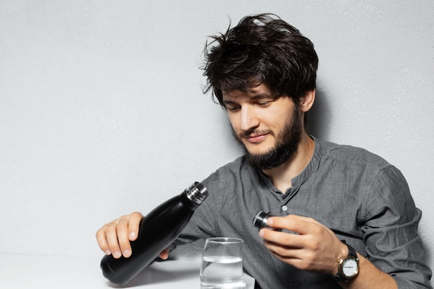 Retrato de um jovem barbudo com cabelo desgrenhado, segurando uma garrafa térmica de aço perto de um copo d'água