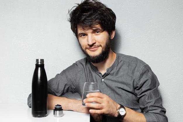 Retrato de um jovem barbudo com cabelo despenteado, segurando um copo de água perto de uma garrafa térmica inoxidável preta.