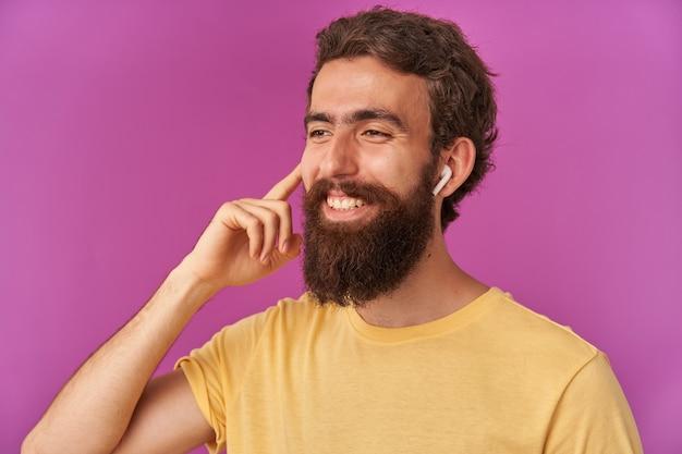 Retrato de um jovem barbudo com os braços usando fones de ouvido olhando e sorrindo à parte, emoção feliz sorrindo confiante