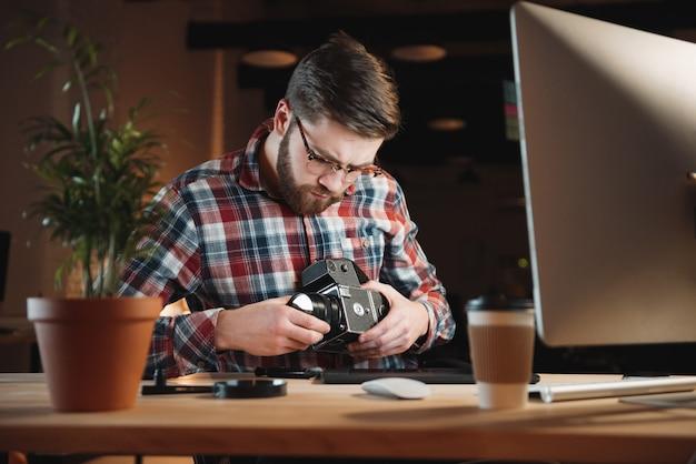 Retrato de um jovem barbudo consertando uma câmera antiga no local de trabalho