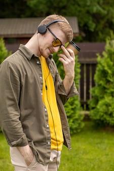 Retrato de um jovem barbudo de óculos e camiseta amarela casualmente vestido de pé com um copo de papel descartável, ouvindo música on-line com fones de ouvido no fundo verde.