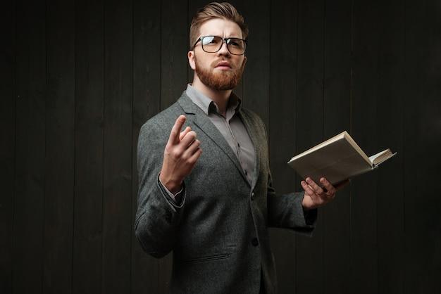 Retrato de um jovem barbudo de óculos e terno casual, aprendendo roteiro isolado no fundo preto de madeira