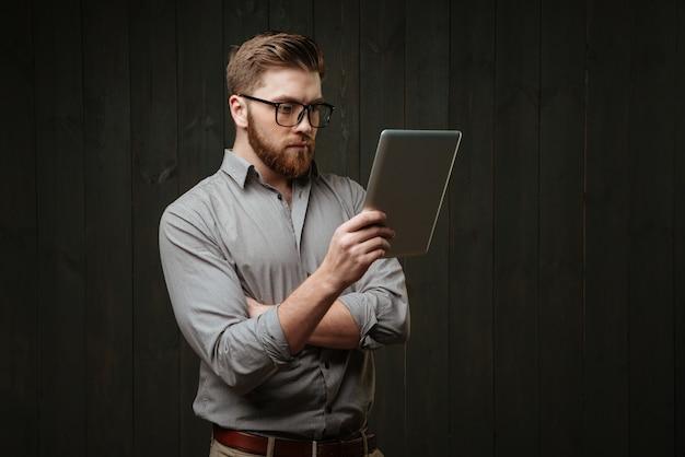 Retrato de um jovem barbudo de óculos, olhando para o computador tablet na mão, isolado na superfície de madeira preta