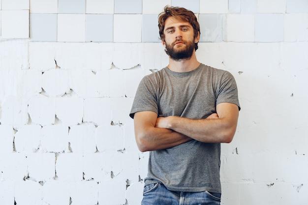 Retrato de um jovem barbudo de pé contra a parede resistida grunge