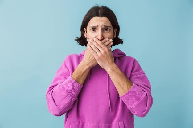 Retrato de um jovem barbudo e confuso, chocado, moreno, usando um moletom, isolado na parede azul, cobrindo a boca