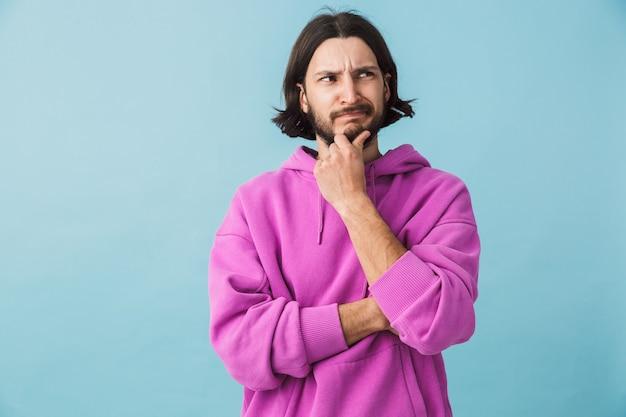 Retrato de um jovem barbudo e frustrado homem moreno usando um capuz isolado na parede azul, pensando