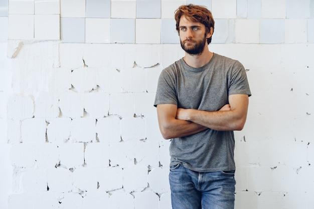 Retrato de um jovem barbudo em pé contra a parede desgastada do grunge