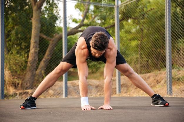 Retrato de um jovem barbudo em roupas esportivas, esticando as pernas ao ar livre