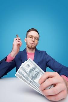 Retrato de um jovem barbudo hipócrita sério de óculos sentado com dinheiro à mesa e fumando charuto